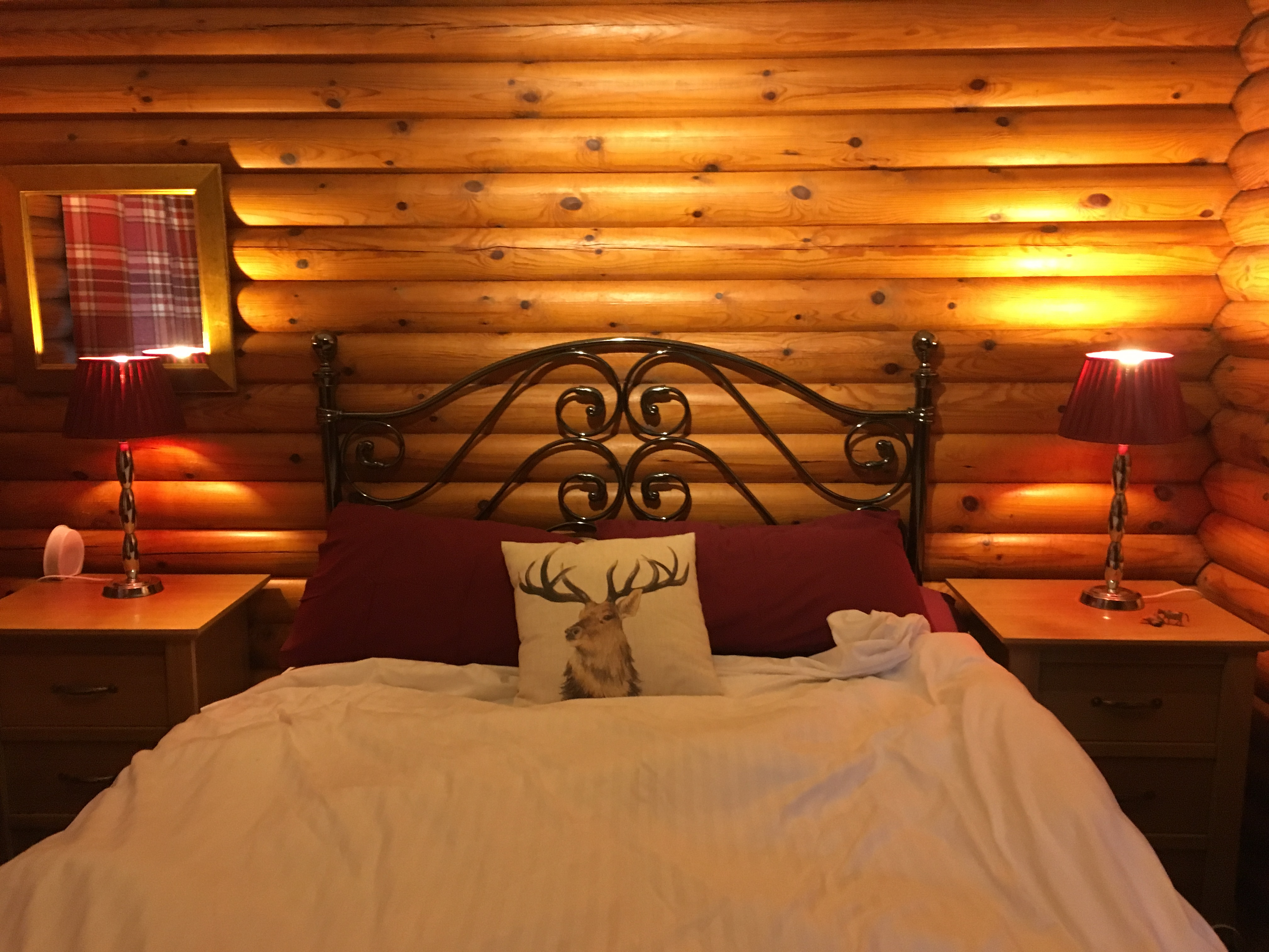 Image of dimly lit bedroom in a log cabin. Complete with a totally adorable reindeer pillow.
